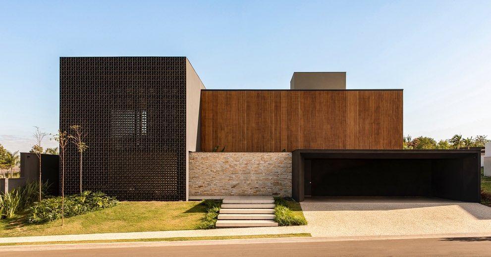 Arquitectos usan ladrillos de cobogó negro y brisas de madera en casas de Brasil